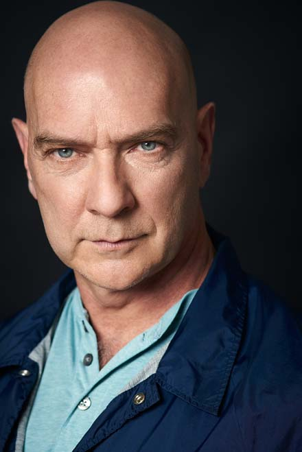 Theatrical headshot of character actor with intense expression and cinematic lighting